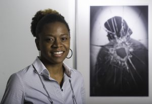 "Celestia Morgan, graduate student, with her photograph, ""B.J.,"" from the series, ""Broken."""