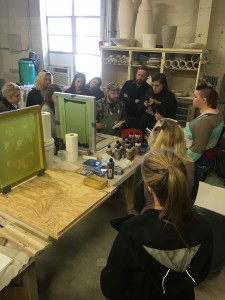 Workshop participants listen in as Israel Davis explains direct screen printing on clay slabs and newsprint transfer