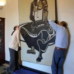 "Emily Bibb and Bill Dooley hang ""Cassandra"" by Ben Smith in the foyer of Morgan Hall."