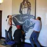 "Emily Bibb and Bill Dooley hang ""Cassandra"" in the foyer of Morgan Hall."