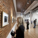 A student looks at work in an exhibition at the Paul R. Jones Gallery.