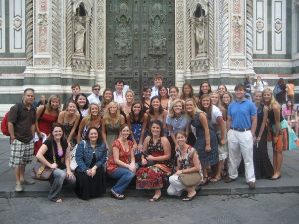 a large group of students posing outside an old building