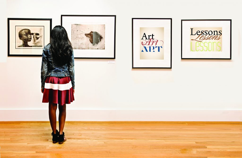 A student looks at an exhibition in the Paul R. Jones Gallery.