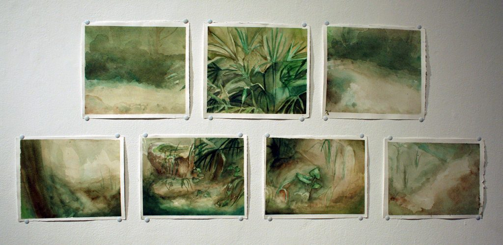 a collection of paintings hanging on a wall