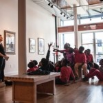 Lucy Curzon and Katie Howard speak to middle school children about art works on display at the Paul R. Jones Gallery of Art in Tuscaloosa.