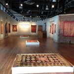 colorful rugs hanging on gallery walls and arranged on platforms