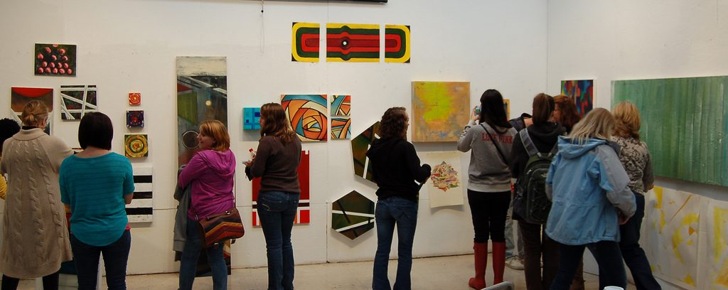 Painting students looking at each others' work pinned to the wall.