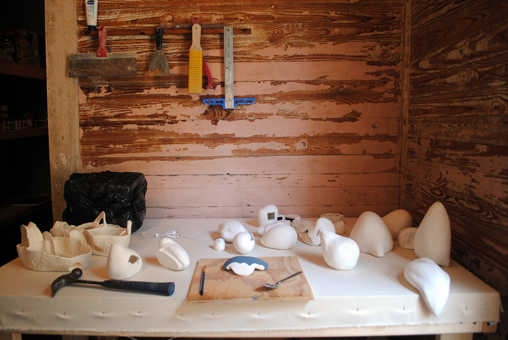 Virginia Eckinger's work table, covered in ceramic pieces ready for painting, at The Grocery.