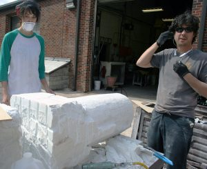 two sculptors working on a large chunk of white marble
