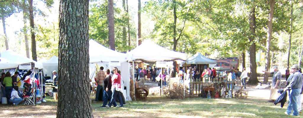 White tents of arts and crafts vendors under the trees.