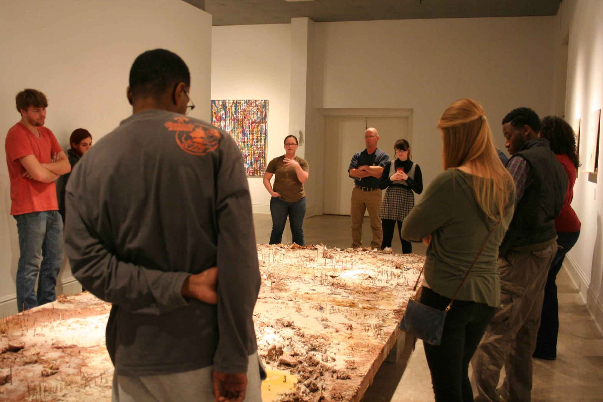 Class critiquiing work by Heather Leigh Whidden; painting by Joshua Whidden in background, in Bilateral; Memory & Experience, 2015, Sella-Granata Art Gallery.