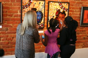 Gallery manager Katie Howard (left) talks to middle and elementary kids at the Paul Jones Gallery about the art.