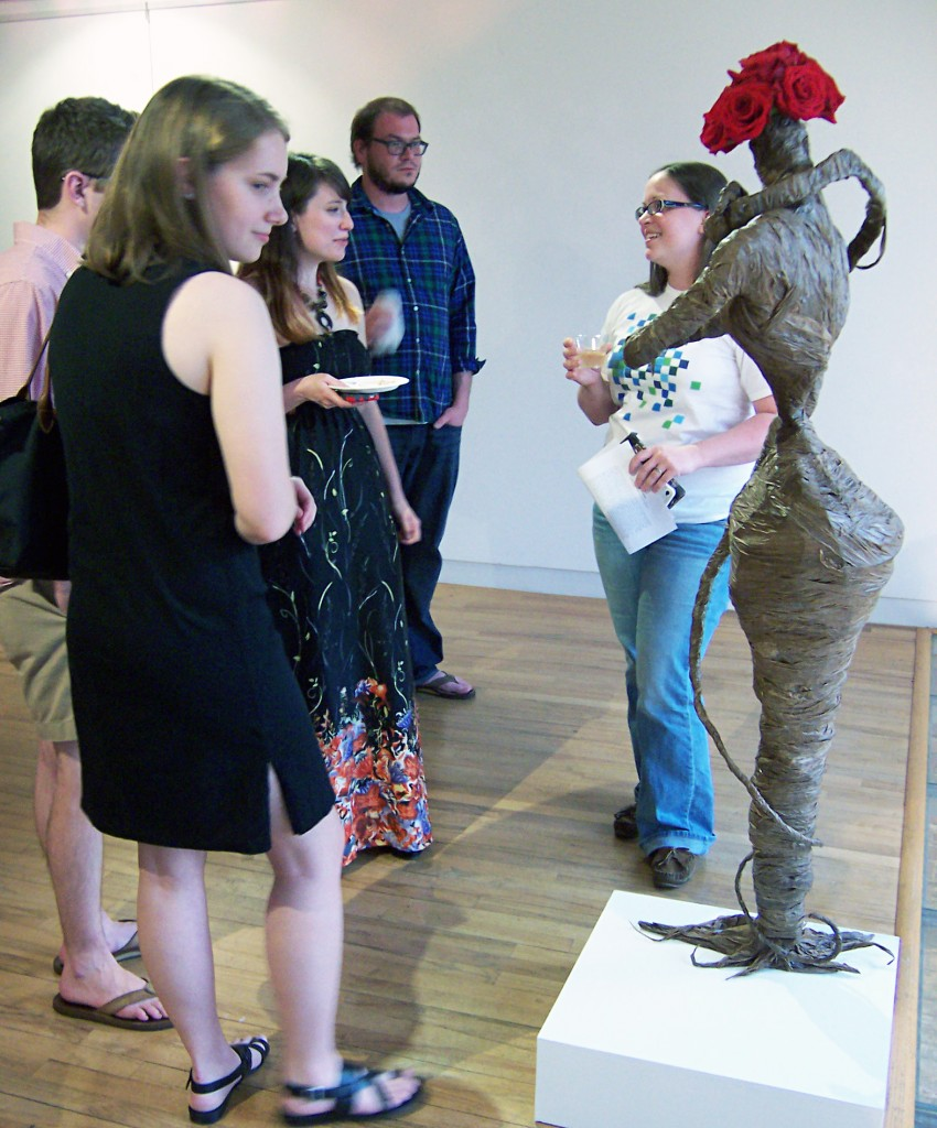 Ali Jackson (center) talking with visitors at her BFA exhibition at Harrison Galleries.