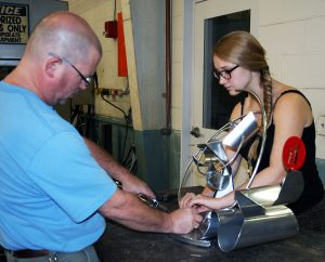 Craig Wedderspoon helps Alli Sloan put finishing touches on her steel sculpture for Nucor Children's of Alabama charity auction.