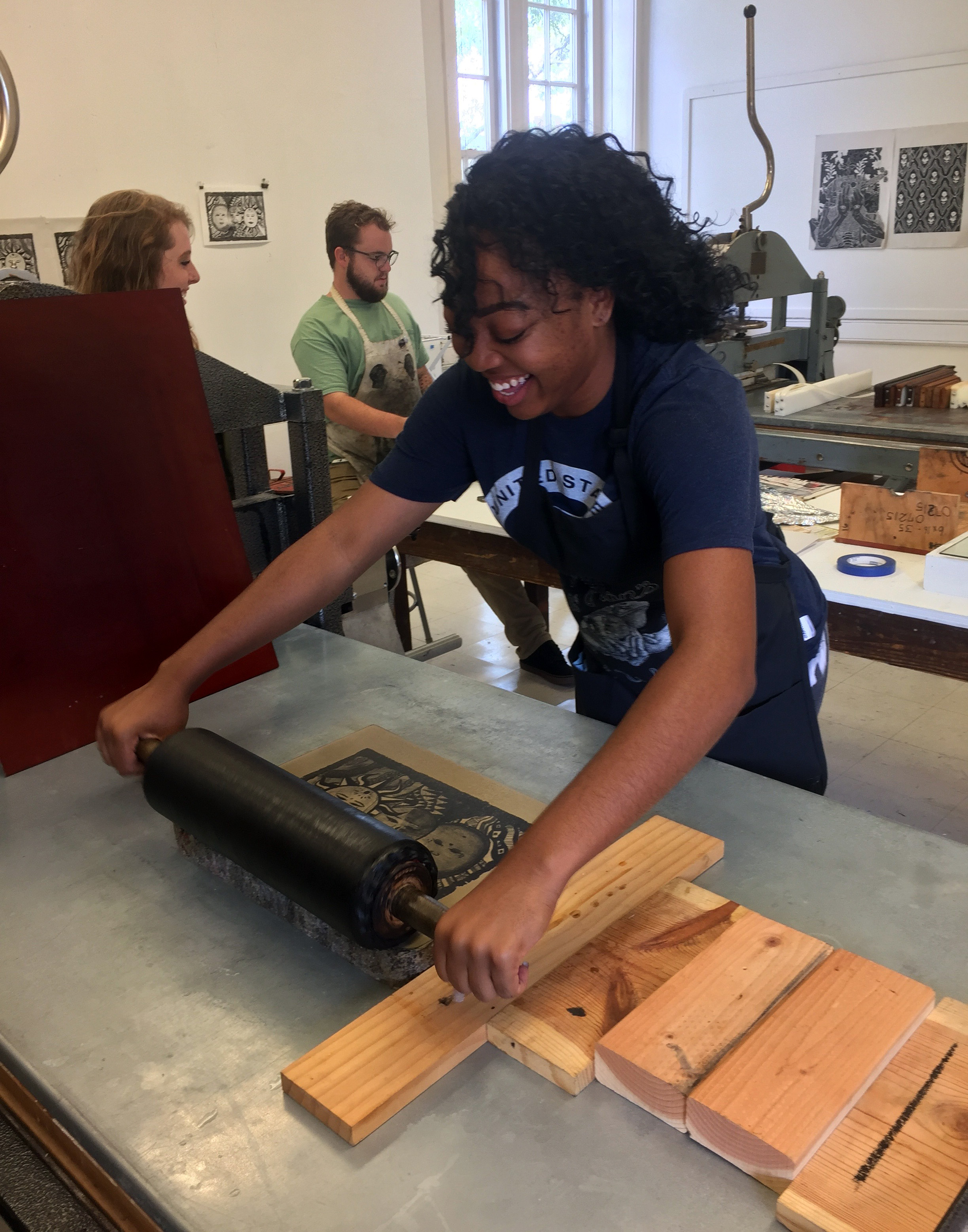 Kenya Russel, ART 321 Lithography, rolls up her stone in the litho shop.
