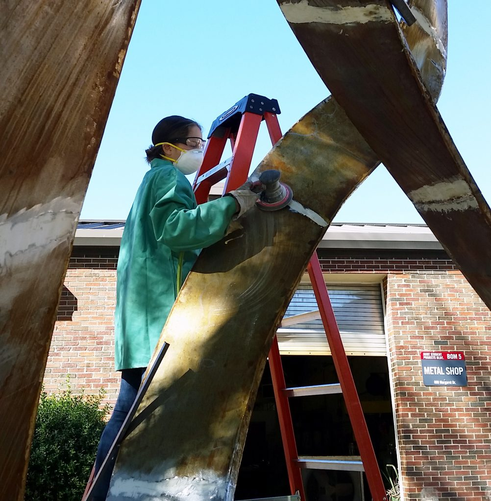 "Paget Kern working on her sculpture, ""Mobius and Borromean Rings,"" welded steel, now in the Woods Quad Sculpture Garden"