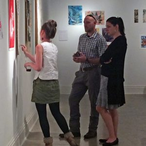 A BFA major talks to visitors about her work on exhibit in the gallery.