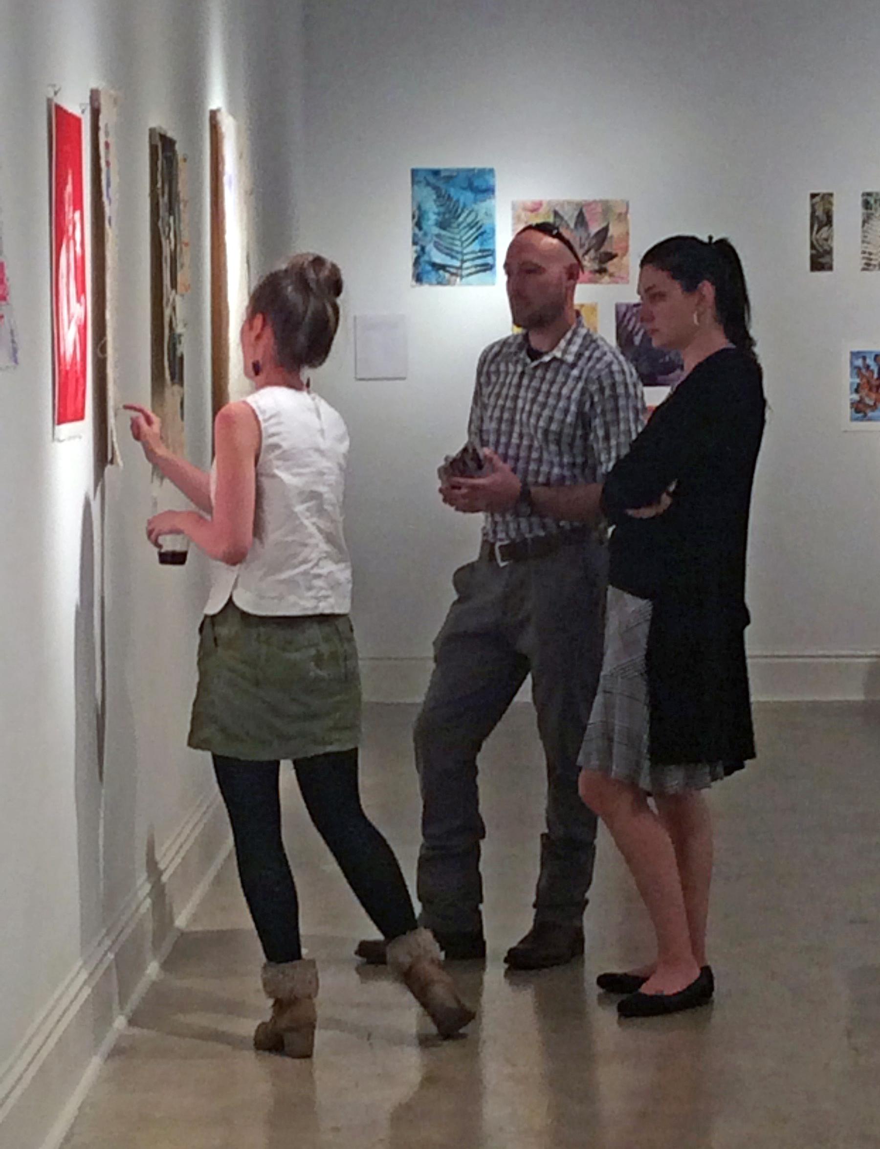 Rachel Jones, BFA major talks to gallery visitors about her work.