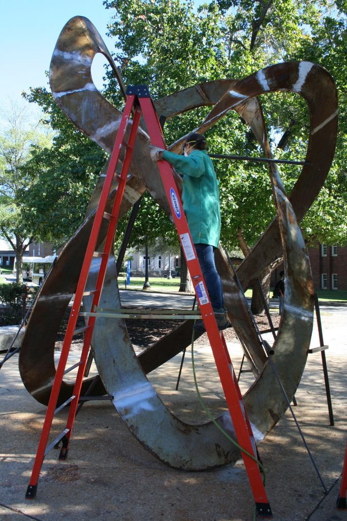 """Paget Kern working on her sculpture, """"Mobius and Borromean Rings,"""" outside the UA art foundry. It is now in the Woods Quad Sculpture Garden."""