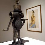 """Foreground: Frank Fleming, """"Mr. Peanut with Golden Egg,"""" n.d., cast bronze (lost wax), Gift of Morgan Estate; background: Alice Neel, """"Man in Harness,"""" 1980, color lithograph, Gift of Matthew Mosca."""