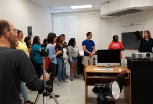 Professors Chris Jordan and Allison Grant give Booker T. Washington Magnet High School photography students a tour of photo facilities in Woods Hall.