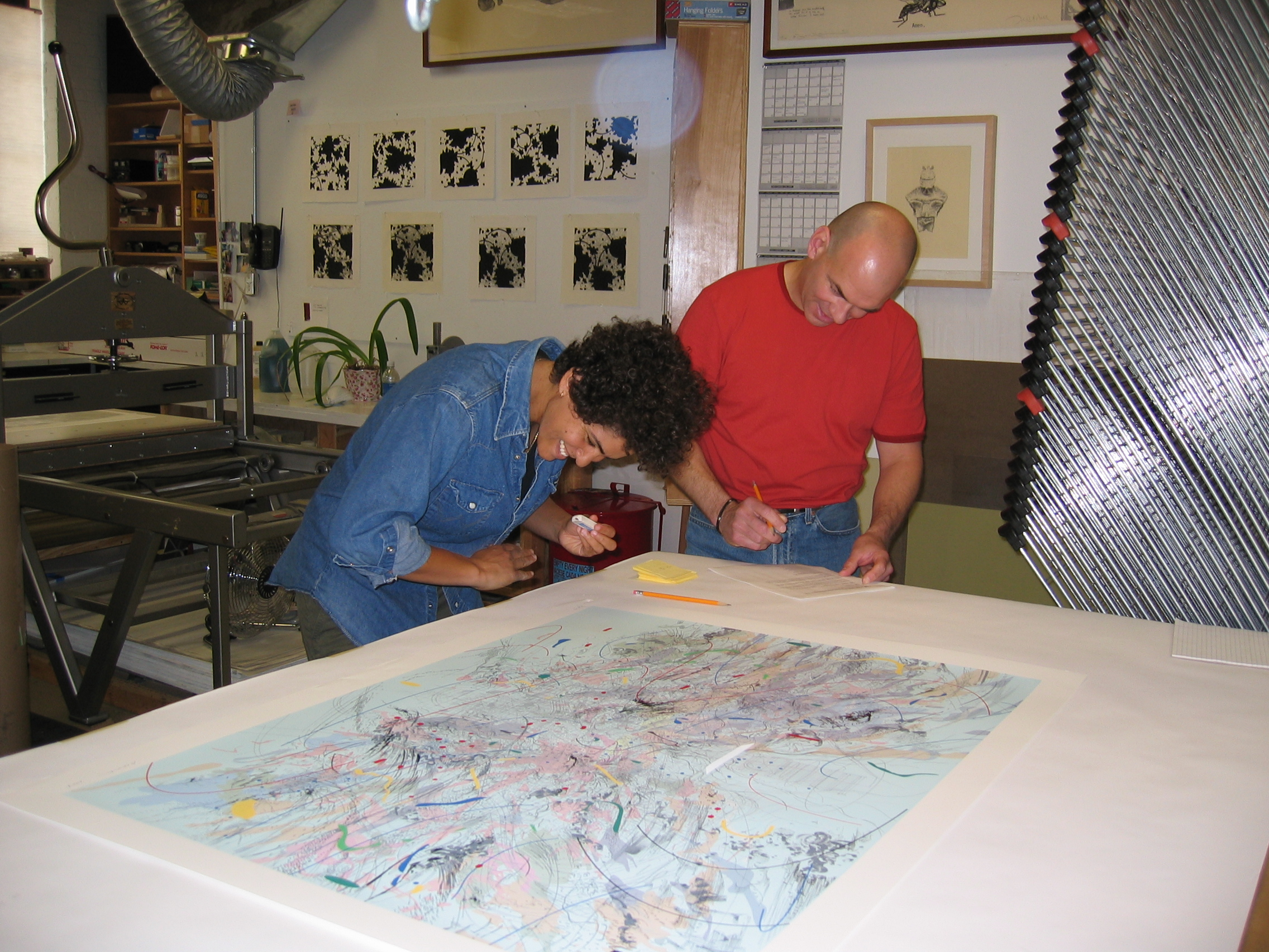 Artist Julie Mehretu and master printer Cole Rogers work on her print exhibition. Mehretu's prints are on exhibit in the Sarah Moody Gallery of Art, January 24 through March 8, 2019.
