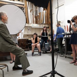 faculty member, seated, has his photo taken by students