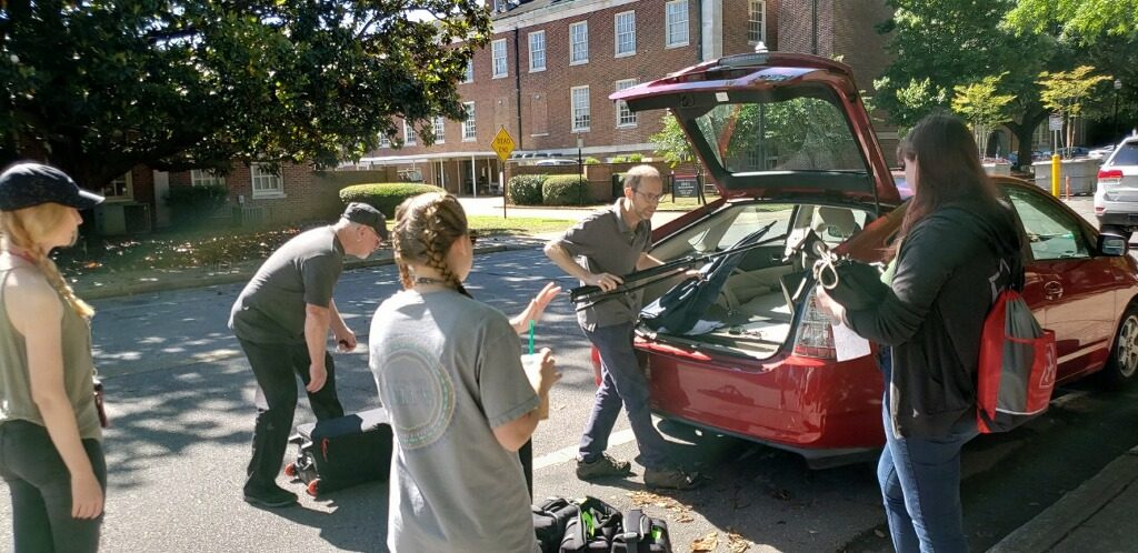 Associate Professor Chris Jordan and students load photographic equipment into the car before their trip to Wilcox County, Ala.