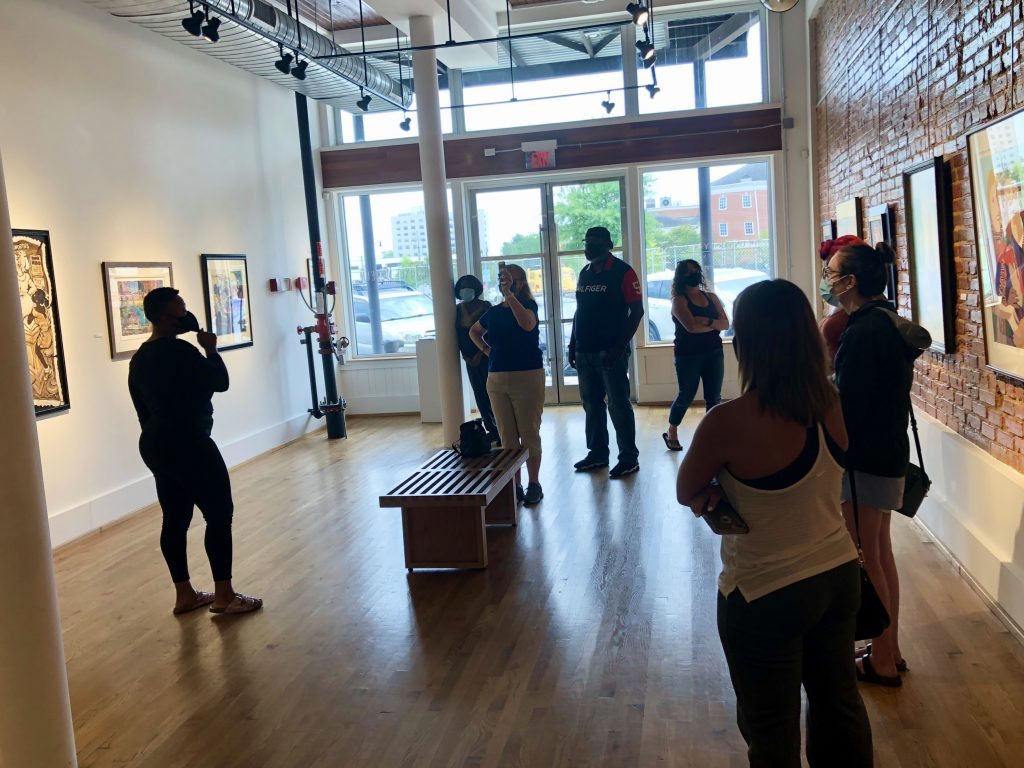 Visitors look at artwork in a gallery