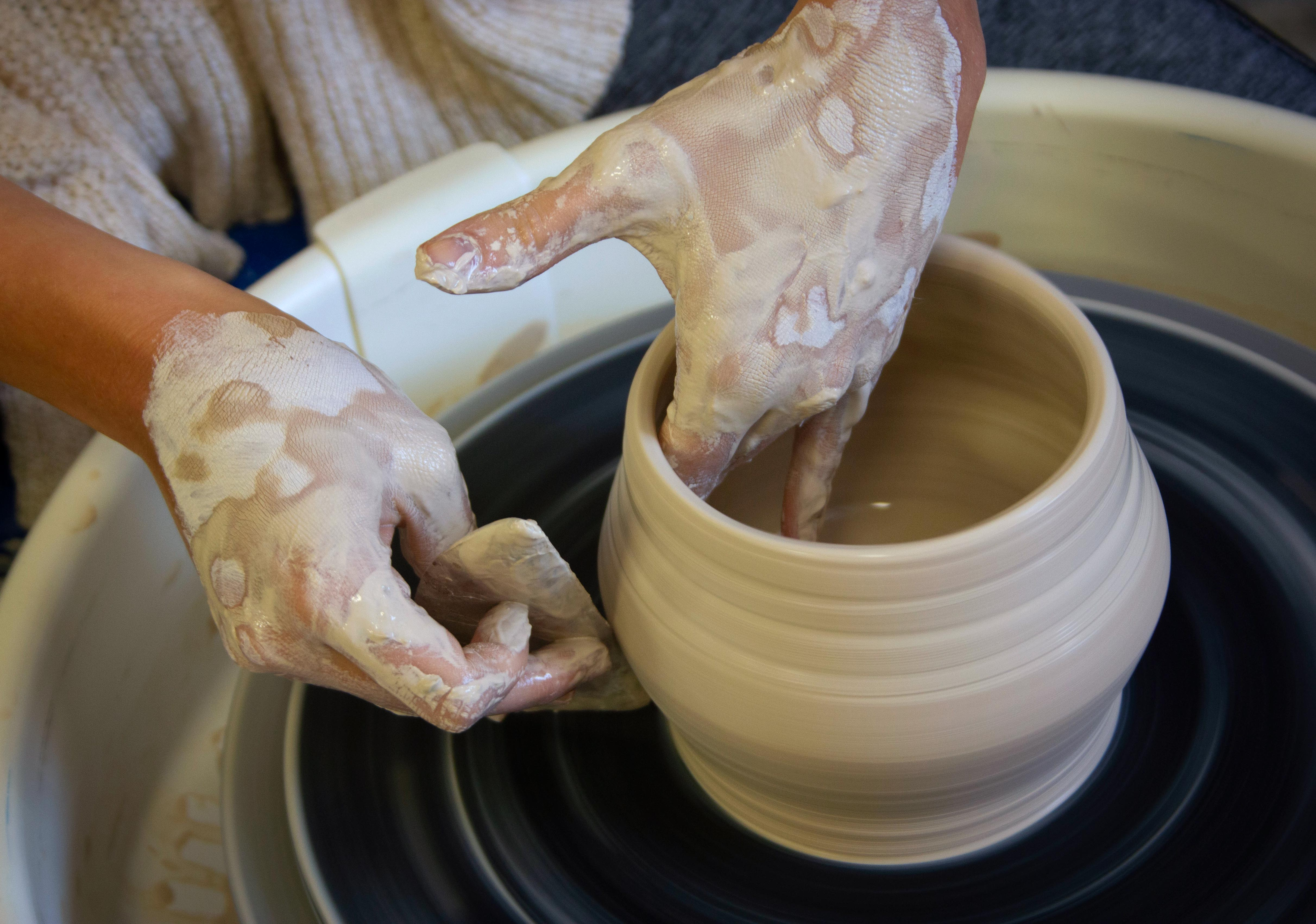 close-up view of a student spinning pottery
