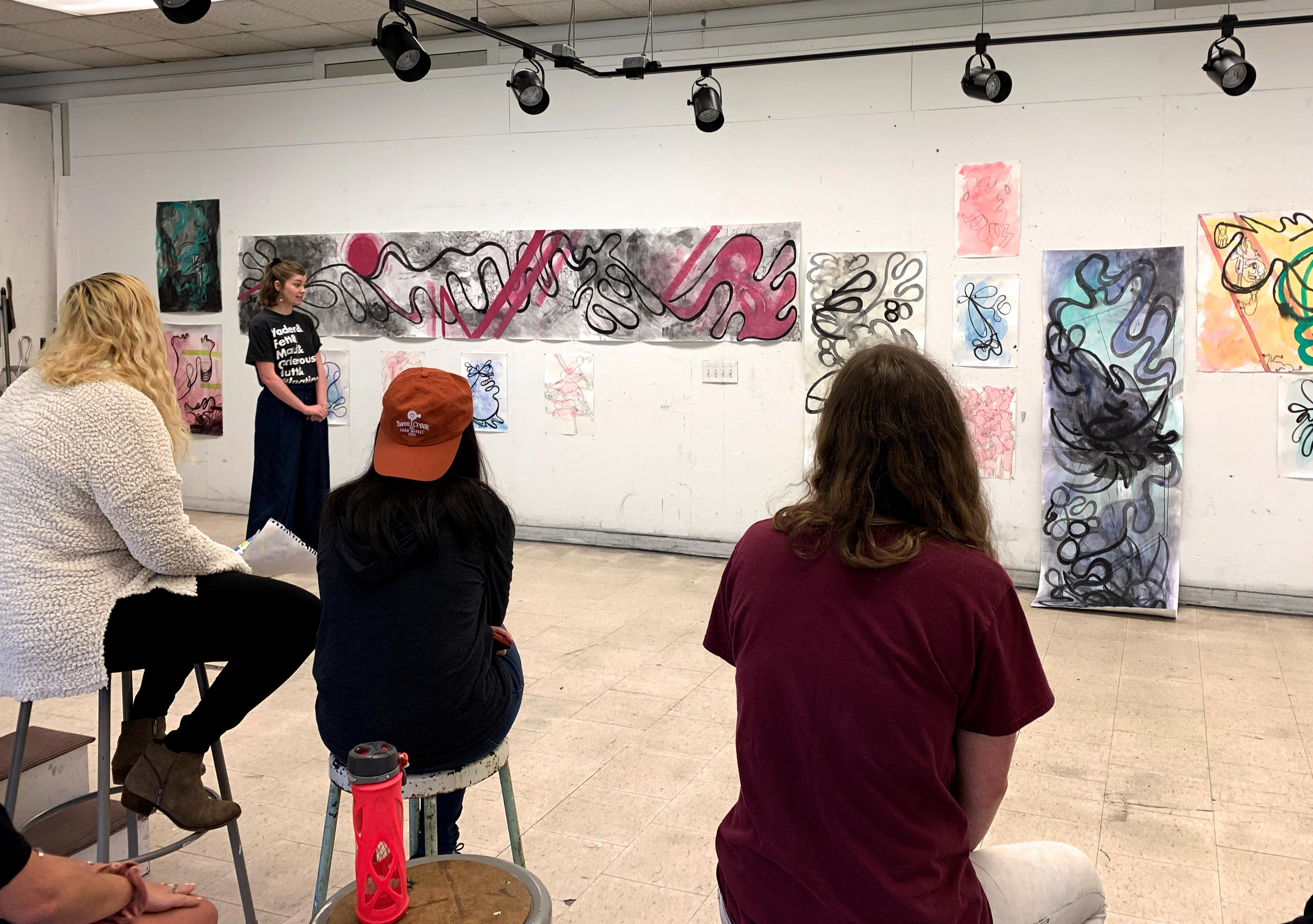 students gathered in studio for a critique