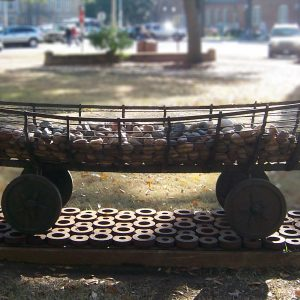a sculpture resembling a canoe on wheels, filled with rocks