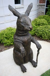 metal sculpture of a rabbit carrying a walking stick