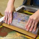 a student spreading ink across a screen printing screen