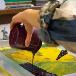 student pouring ink onto a surface