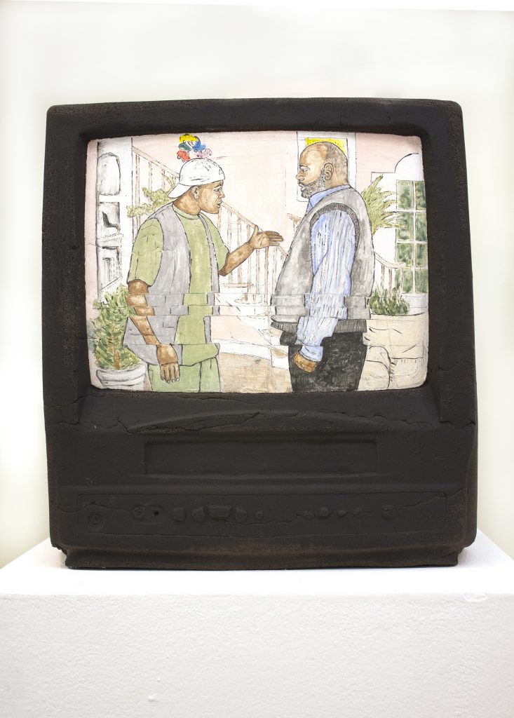 Sculpture of a television depicting a TV show scene between a younger black man and an older black man.