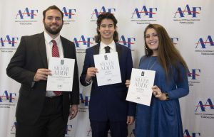 Three winners stand for a photo with their award certificates.