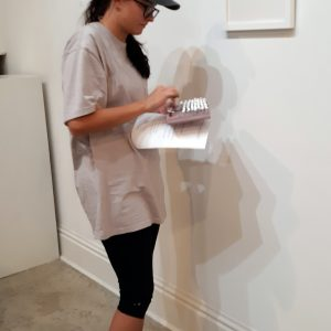 A student gallery worker attaches labels to the wall next to an artwork.