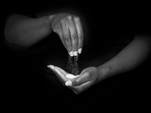 An African American sifting salt from one hand to the palm of another hand.