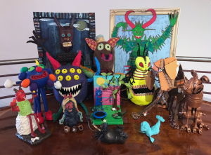 Several scary handmade monsters pose for their picture in an art gallery.