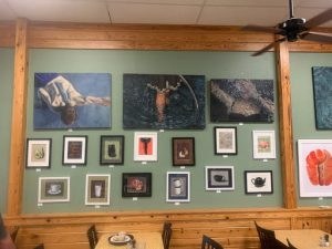 Paintings displayed on a restaurant wall.