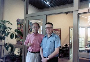 Two art professors stand in a gallery doorway.