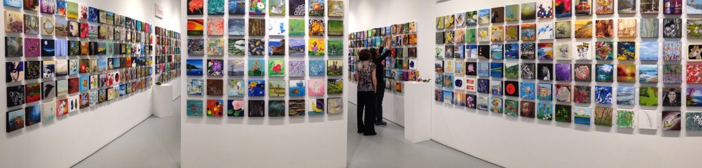 three walls filled with small square colorful paintings.