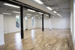 An open and brightly lit room with white walls and wood floors.