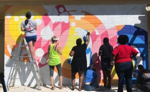 White and black people painting an outdoor mural together.