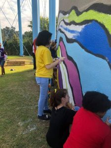 White and black people painting an outdoor mural together
