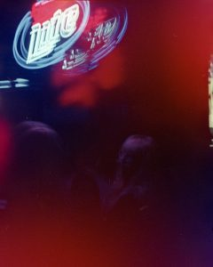 """People sitting in a blurry, dark room lit by a neon """"Lite"""" beer sign."""