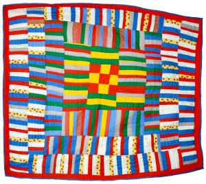 A brightly colored quilt made up of horizontal and uneven patches.