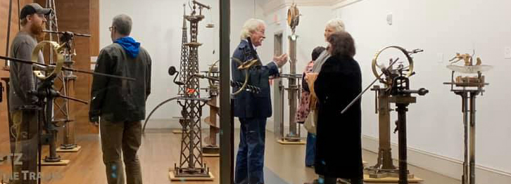 Visitors standing among large metal sculptures in a gallery.