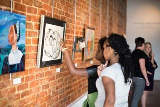 two students examine a drawing hanging on a wall
